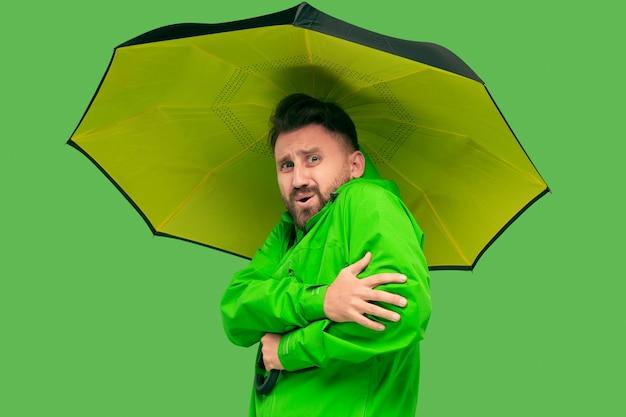 Hübscher bärtiger frierender junger mann, der regenschirm hält und kamera lokalisiert auf lebendigem trendigem grünem studio betrachtet. Kostenlose Fotos