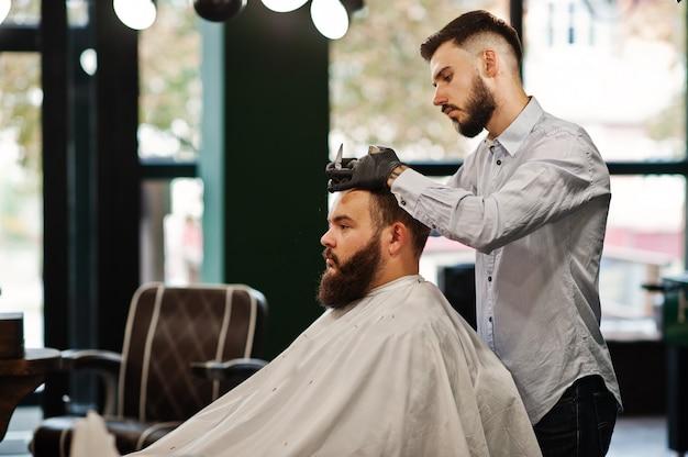 Hübscher bärtiger mann am friseursalon, friseur bei der arbeit. Premium Fotos