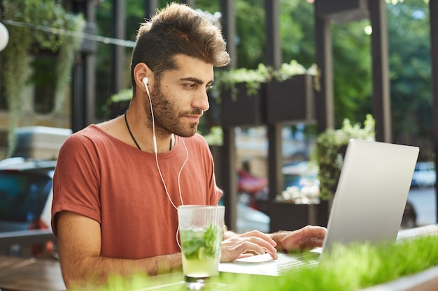 Hübscher bärtiger mann, freiberufler, der fern vom straßencafé arbeitet, programmierer mit laptop, der musik hört, um sich auf arbeit zu konzentrieren Kostenlose Fotos
