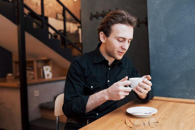 Hübscher bärtiger mann im karierten hemd, das gabel hält, das im café isst und lächelt Kostenlose Fotos