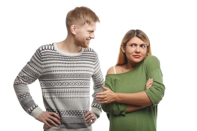 Hübscher bärtiger mann im pullover, der lächelt und eine attraktive frau ansieht, die in geschlossener haltung mit verschränkten armen steht und sich verwirrt fühlt, weil sie seinen albernen witz nicht mag oder versteht Kostenlose Fotos