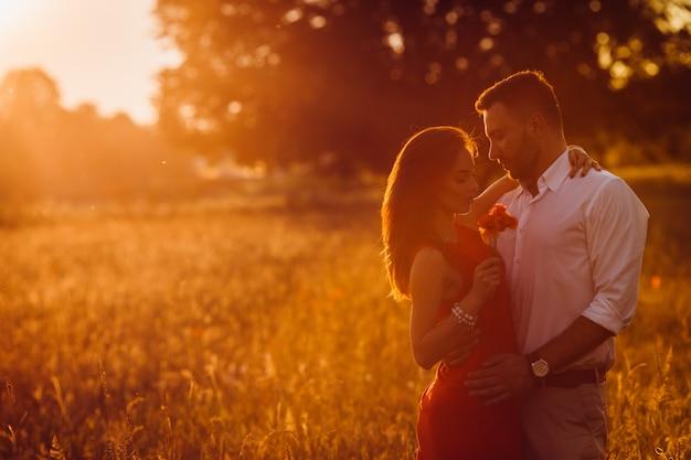 Hübscher bärtiger mann umarmt frau im roten kleiderangebot, das auf dem goldenen sommergebiet steht Kostenlose Fotos