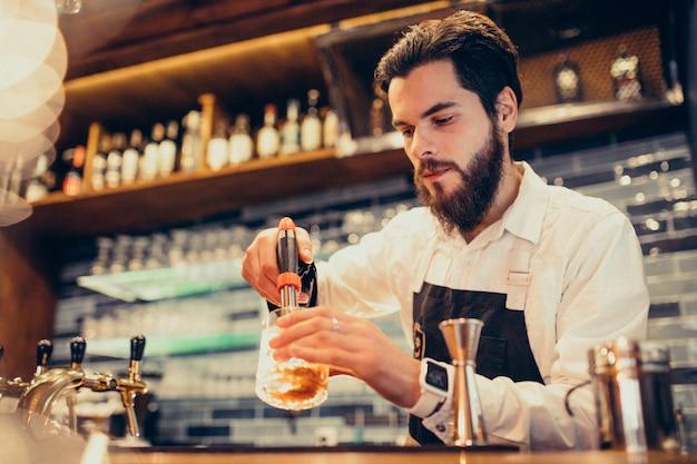 Hübscher barmixer, der das trinken und die cocktails an einem zähler macht Kostenlose Fotos