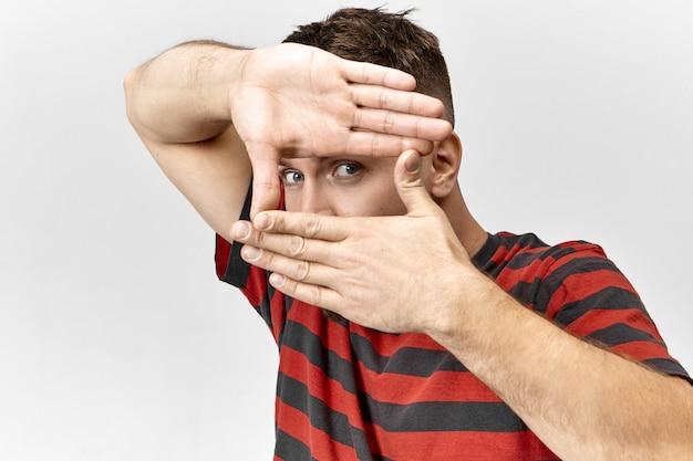 Hübscher blauäugiger fotograf in stilvollem t-shirt, der mit seinen händen einen fotorahmen macht, sich auf die augen konzentriert und den schülern das fotografieren beibringt. menschen, lebensstil, spaß und körpersprache Kostenlose Fotos