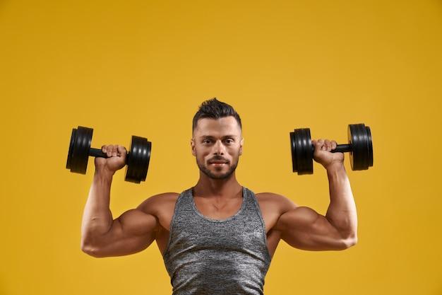 Hübscher bodybuilder, der mit hanteln trainiert Premium Fotos