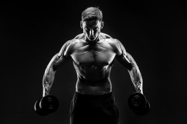 Hübscher bodybuilder, der übung mit dummkopf tut. Premium Fotos