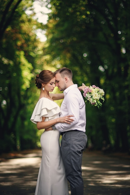 Hübscher bräutigam, der seine schöne atemberaubende braut mit blumenstrauß im romantischen europäischen park umarmt Premium Fotos