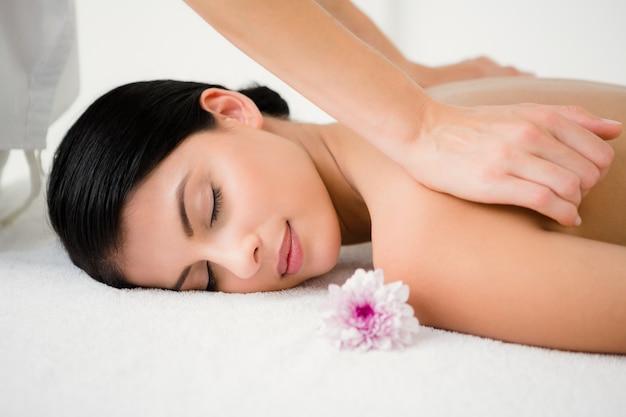 Hübscher brunette, der eine massage mit blume genießt Premium Fotos