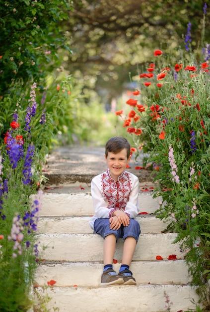 Hübscher brunettejunge 5-6 jahre alt in einem traditionellen kostüm auf einem mohnblumengebiet im sommer Premium Fotos
