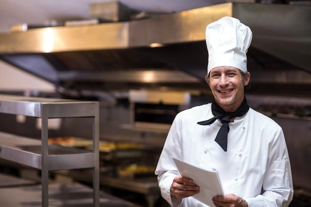 Hübscher chef, der menü hält Premium Fotos