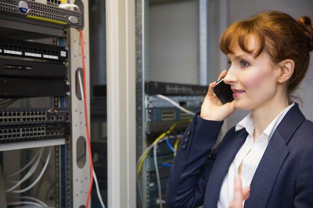 Hübscher computertechniker, der am telefon neben offenem server spricht Premium Fotos