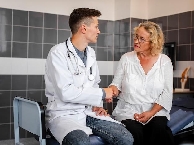 Hübscher doktor, der hand mit patienten rüttelt Kostenlose Fotos
