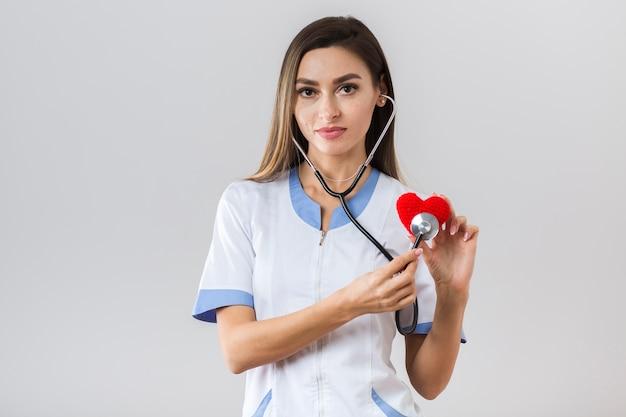 Hübscher doktor der vorderansicht, der ein plüschherz hält Kostenlose Fotos