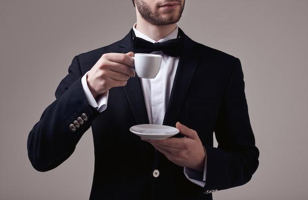 Hübscher eleganter mann mit dem gelockten haar im smoking, das eine tasse espresso hält Premium Fotos