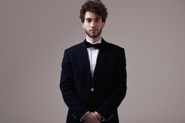 Hübscher eleganter mann mit tragendem smoking des gelockten haares Premium Fotos