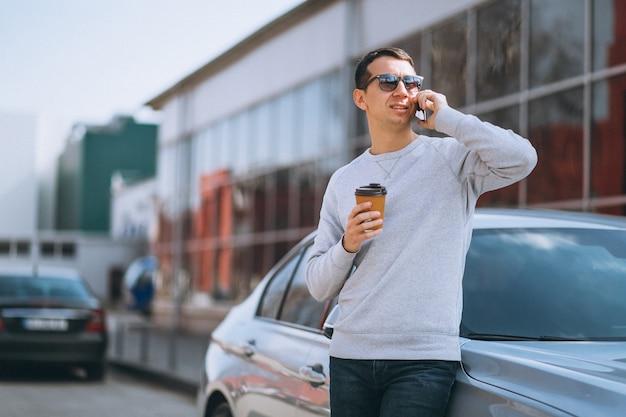Hübscher erfolgreicher mann mit dem auto mit mobiltelefon Kostenlose Fotos