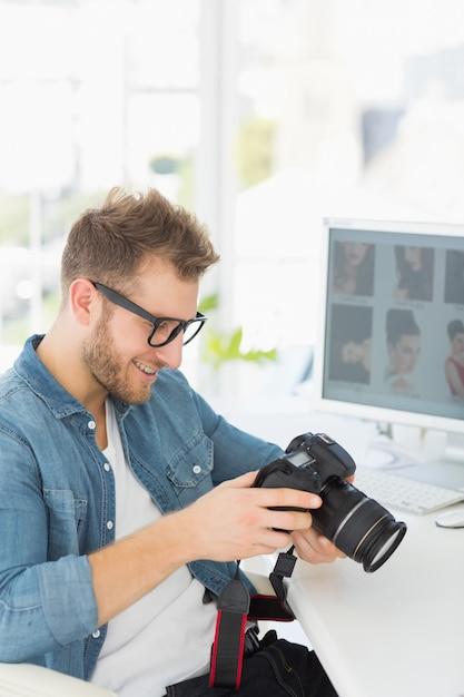 Hübscher fotograf, der seine kamera und lächeln hält Premium Fotos