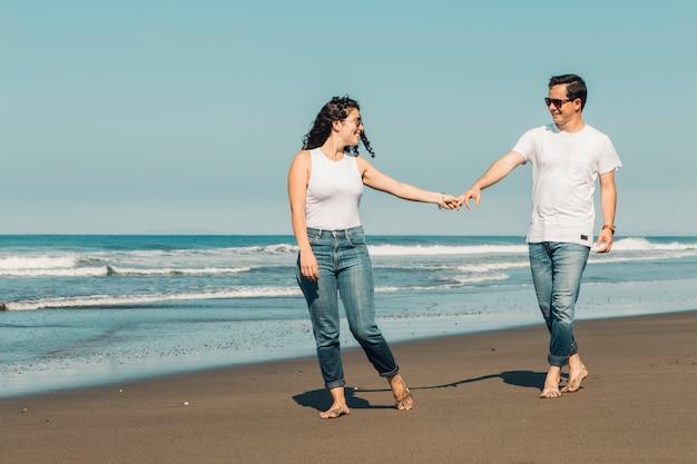 Hübscher frau, die mann wünscht, folgen auf sandigem strand Kostenlose Fotos