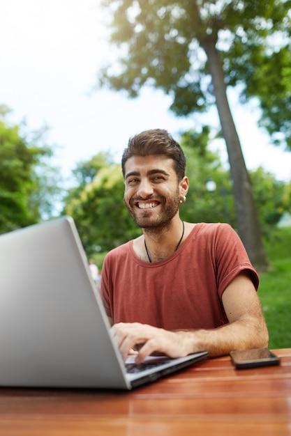 Hübscher freiberufler, der fern arbeitet, auf parkbank mit laptop sitzt, wifi verbindet Kostenlose Fotos