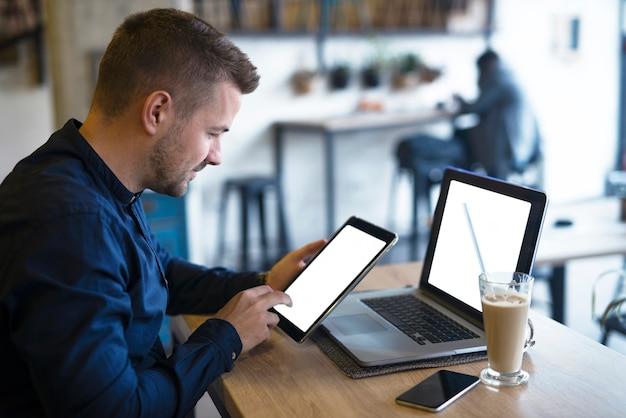 Hübscher freiberufler, der tablet- und laptop-computer verwendet, um sein geschäft im café zu überprüfen Kostenlose Fotos