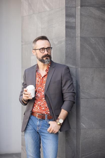 Hübscher fröhlicher mann, der nahe bürogebäude steht, das wegwerfbecher kaffee hält Premium Fotos