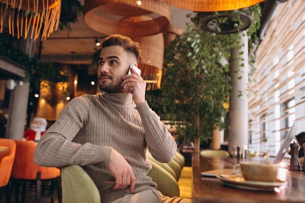 Hübscher geschäftsmann, der an computer arbeitet und kaffee in einem café trinkt Kostenlose Fotos