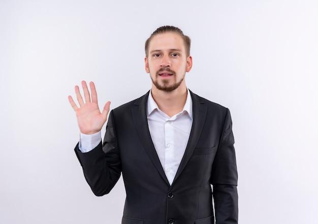 Hübscher geschäftsmann, der anzug trägt, der nummer fünf lächelnd zuversichtlich über weißem hintergrund stehend zeigt Kostenlose Fotos