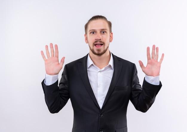 Hübscher geschäftsmann, der anzug zeigt, der nummer zehn lächelnd fröhlich stehend über weißem hintergrund zeigt Kostenlose Fotos