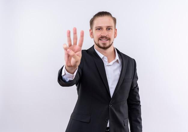 Hübscher geschäftsmann, der anzug zeigt und mit den fingern nummer drei über weißem hintergrund stehend zeigt Kostenlose Fotos