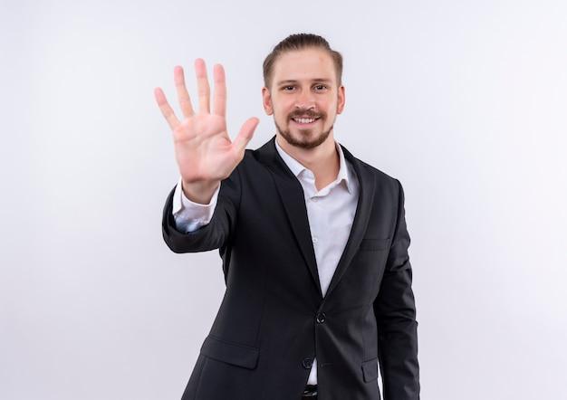Hübscher geschäftsmann, der anzug zeigt und mit den fingern nummer fünf über weißem hintergrund stehend zeigt Kostenlose Fotos