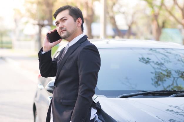 Hübscher geschäftsmann, der einen handy lerning auf seinem auto verwendet Premium Fotos