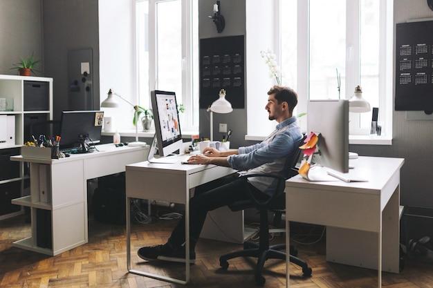 Hübscher geschäftsmann, der im büro arbeitet Kostenlose Fotos