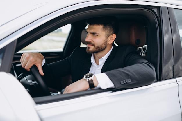 Hübscher geschäftsmann, der in ein auto reist Kostenlose Fotos