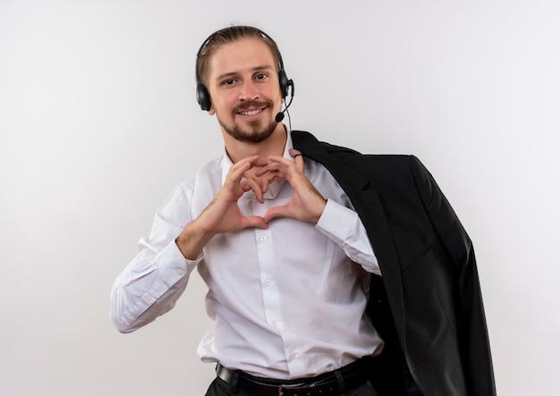 Hübscher geschäftsmann, der jacke über schulter mit kopfhörern mit einem mikrofon hält, das herzgeste mit den lächelnden fingern macht, die über weißem hintergrund stehen Kostenlose Fotos