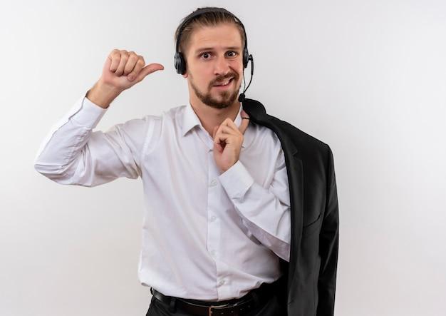Hübscher geschäftsmann, der jacke über schulter mit kopfhörern mit einem mikrofon hält, das kamera betrachtet, verwirrt über weißem hintergrund steht Kostenlose Fotos