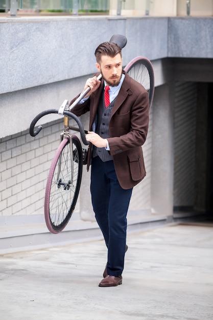 Hübscher geschäftsmann, der sein fahrrad auf stadtstraßen trägt. das konzept des modernen lebensstils junger männer Kostenlose Fotos