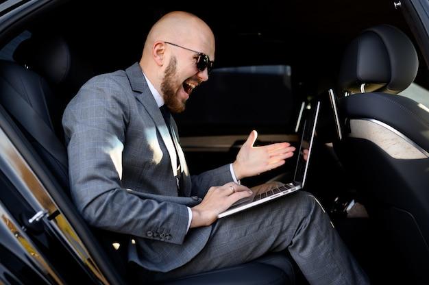 Hübscher geschäftsmann, der sein handy in einem modernen auto mit einem fahrer im zentrum der stadt benutzt. geschäftskonzept Premium Fotos