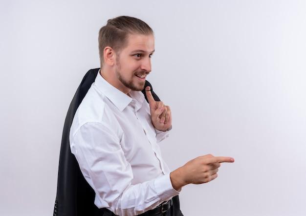 Hübscher geschäftsmann, der seine jacke auf der schulter trägt, die lächelnd schaut und mit dem finger zur seite zeigt, die über weißem hintergrund steht Kostenlose Fotos