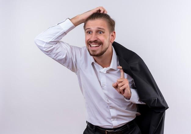 Hübscher geschäftsmann, der seine jacke auf der schulter trägt und verwirrt und sehr besorgt über weißem hintergrund beiseite schaut Kostenlose Fotos