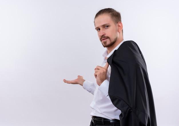 Hübscher geschäftsmann, der seine jacke auf schulter lächelnd lächelnd etwas mit arm seiner hand über weißem hintergrund stehend trägt Kostenlose Fotos
