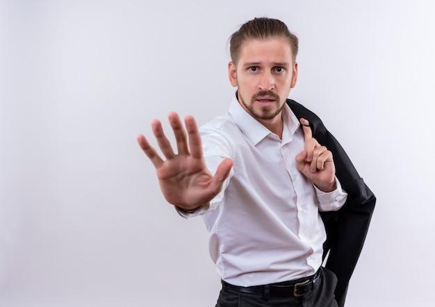 Hübscher geschäftsmann, der seine jacke auf schulter macht stoppschild mit hand, die mit ernstem gesicht steht, das über weißem hintergrund steht Kostenlose Fotos