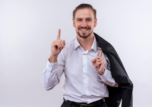 Hübscher geschäftsmann, der seine jacke auf schulter trägt, die kamera betrachtet, die mit glücklichem gesicht lächelt, zeigefinger zeigt, der neue idee über weißem hintergrund steht Kostenlose Fotos
