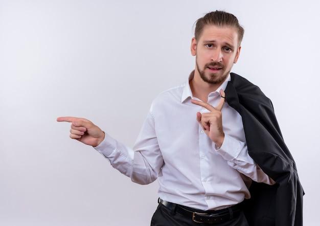 Hübscher geschäftsmann, der seine jacke auf schulter trägt, die kamera lächelnd sicher zeigt mit feigen auf die seite steht über weißem hintergrund Kostenlose Fotos