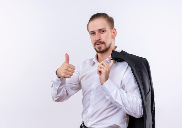 Hübscher geschäftsmann, der seine jacke auf schulter trägt, die kamera mit dem selbstbewussten lächeln betrachtet, das daumen oben zeigt über weißem hintergrund Kostenlose Fotos