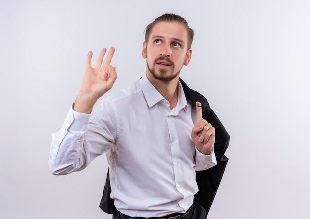 Hübscher geschäftsmann, der seine jacke auf schulter trägt, die lächelnd beiseite zeigt und ok zeichen steht über weißem hintergrund Kostenlose Fotos