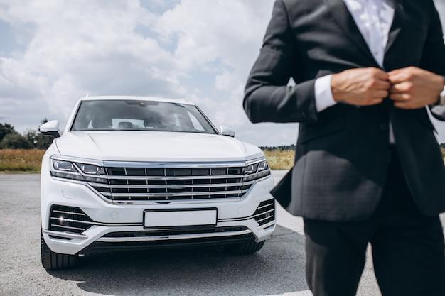 Hübscher geschäftsmann durch das weiße auto Kostenlose Fotos