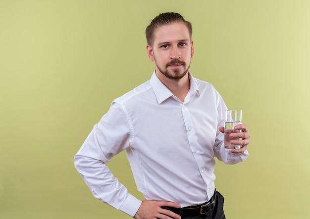 Hübscher geschäftsmann im weißen hemdglas des wassers, das kamera mit dem sicheren ausdruck betrachtet, der über olivenhintergrund steht Kostenlose Fotos