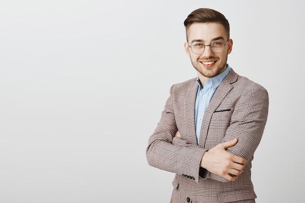 Hübscher geschäftsmann in anzug und brille verschränkt die brust und schaut Kostenlose Fotos