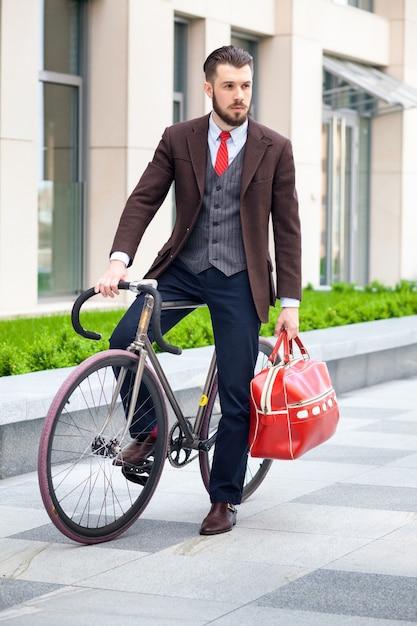 Hübscher geschäftsmann in einer jacke mit roter tasche, die auf seinem fahrrad auf stadtstraßen sitzt. Kostenlose Fotos
