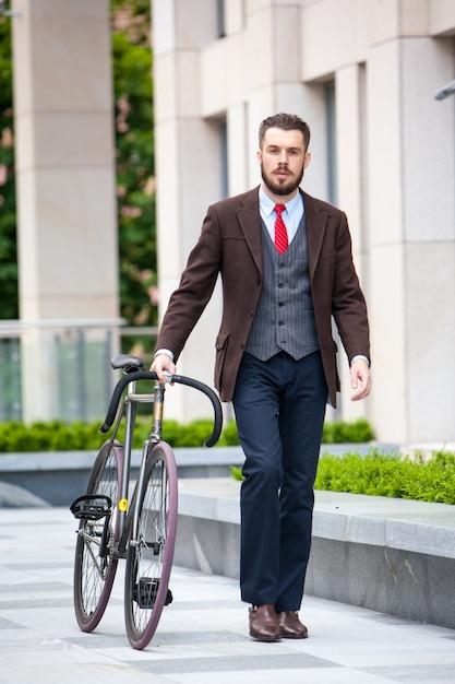 Hübscher geschäftsmann in einer jacke und einer roten krawatte und seinem fahrrad auf den straßen der stadt. Kostenlose Fotos